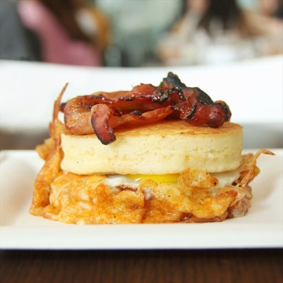 Thick layers of pancakes sandwiched with a fried egg